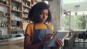 Νέος θηλυκός ιδιοκτήτης που χρησιμοποιεί την ψηφιακή ταμπλέτα στεμένος στον καφέ απόθεμα βίντεο
