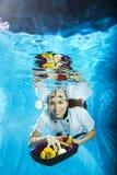 Νέος θηλυκός μάγειρας που κολυμπά με ένα πράσινο μήλο και έναν πιό magnifier στοκ εικόνα με δικαίωμα ελεύθερης χρήσης