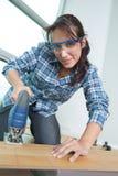 Νέος θηλυκός ξυλουργός που χρησιμοποιεί τη μηχανή στο εργαστήριο Στοκ Εικόνες