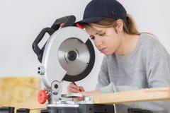 Νέος θηλυκός ξυλουργός που χρησιμοποιεί το κυκλικό πριόνι που κόβει Στοκ φωτογραφία με δικαίωμα ελεύθερης χρήσης