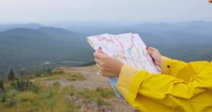 Νέος θηλυκός οδοιπόρος που εξετάζει το χάρτη από την κορυφή βουνών απόθεμα βίντεο