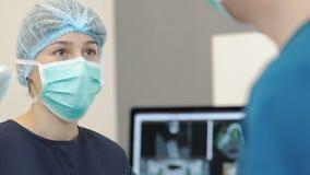 Νέος θηλυκός οδοντίατρος στις προσεγγίσεις μασκών με τα εργαλεία Πρόσωπο οδοντιάτρου φιλμ μικρού μήκους