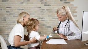 Νέος θηλυκός παιδίατρος που κάνει τους φίλους με το λίγο όμορφο κορίτσι και το mom της στην κλινική υγειονομικής περίθαλψης Φιλικ απόθεμα βίντεο