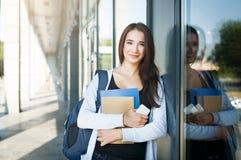 Νέος θηλυκός σπουδαστής ΤΠ, με τα βιβλία, το smartphone και το σακίδιο πλάτης Να μείνει έξω πριν από το μάθημα και χαμόγελο στοκ εικόνα με δικαίωμα ελεύθερης χρήσης
