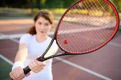 Νέος θηλυκός τενίστας με τη ρακέτα αντισφαίρισης που προετοιμάζεται να εξυπηρετήσει Στοκ Εικόνες