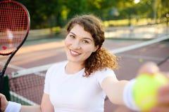 Νέος θηλυκός τενίστας με τη σφαίρα αντισφαίρισης και ρακέτα που προετοιμάζεται να εξυπηρετήσει Στοκ φωτογραφία με δικαίωμα ελεύθερης χρήσης