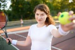 Νέος θηλυκός τενίστας με τη σφαίρα αντισφαίρισης και ρακέτα που προετοιμάζεται να εξυπηρετήσει Στοκ εικόνα με δικαίωμα ελεύθερης χρήσης