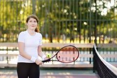 Νέος θηλυκός τενίστας με τη σφαίρα αντισφαίρισης και ρακέτα που προετοιμάζεται να εξυπηρετήσει Στοκ Εικόνα