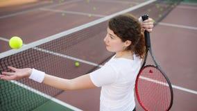 Νέος θηλυκός τενίστας με τη σφαίρα αντισφαίρισης και ρακέτα που προετοιμάζεται να εξυπηρετήσει Στοκ Εικόνες