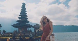 Νέος θηλυκός τουρίστας στο ναό Ulun Danu Batur στην Ινδονησία, στο νησί του Μπαλί Πνευματική και γνωστή θέση Τρόπος ζωής, tra Στοκ Εικόνες