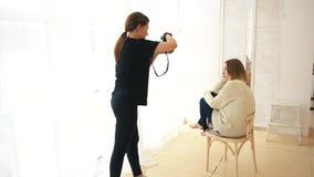 Νέος θηλυκός φωτογράφος που παίρνει την εικόνα του προτύπου χαμόγελου στον άσπρο άλτη και τα σκοτεινά τζιν που κάθονται στον ξύλι απόθεμα βίντεο