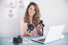 Νέος θηλυκός φωτογράφος που συνδέει το φακό καμερών με τη κάμερα BO στοκ φωτογραφία με δικαίωμα ελεύθερης χρήσης