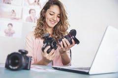 Νέος θηλυκός φωτογράφος που συνδέει το φακό καμερών με τη κάμερα BO στοκ φωτογραφία