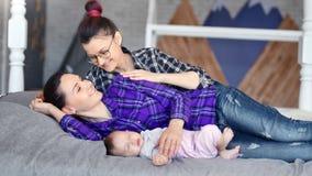 Νέος θηλυκός ύπνος θαυμασμού γονέων δύο hipster λίγο μωρό που βρίσκεται στη μέση απόμακρη πιθανότητα κρεβατιών μαζί απόθεμα βίντεο