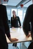 Νέος θηλυκός ανώτερος υπάλληλος με τους συναδέλφους γύρω από έναν πίνακα Στοκ Φωτογραφίες
