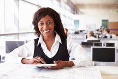 Νέος θηλυκός αρχιτέκτονας που εργάζεται στο γραφείο, που κοιτάζει στη κάμερα Στοκ εικόνα με δικαίωμα ελεύθερης χρήσης