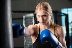 Νέος θηλυκός εγκιβωτισμός σε μια punching τσάντα Στοκ Φωτογραφία