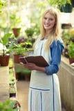 Νέος θηλυκός κηπουρός που εξετάζει τις σε δοχείο εγκαταστάσεις Στοκ φωτογραφία με δικαίωμα ελεύθερης χρήσης