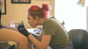 Νέος θηλυκός κοκκινομάλλης καλλιτέχνης δερματοστιξιών που διαστίζει την εικόνα στο πόδι του πελάτη πέρα από το σκίτσο στο στούντι φιλμ μικρού μήκους