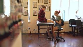 Νέος θηλυκός κοκκινομάλλης καλλιτέχνης δερματοστιξιών που διαστίζει την εικόνα στο πόδι του πελάτη πέρα από το σκίτσο στο στούντι απόθεμα βίντεο