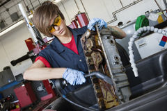 Νέος θηλυκός μηχανικός που εργάζεται με το φανό συγκόλλησης στο μέρος μηχανημάτων οχημάτων στο αυτόματο κατάστημα επισκευής Στοκ Εικόνες
