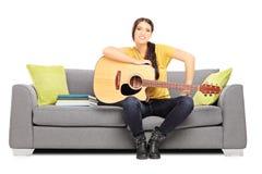Νέος θηλυκός μουσικός που κάθεται σε μια τοποθέτηση καναπέδων με μια κιθάρα Στοκ Εικόνα