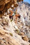 Νέος θηλυκός ορειβάτης βράχου σε έναν απότομο βράχο Στοκ Εικόνες