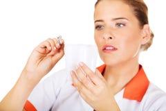 Νέος θηλυκός οδοντίατρος που κρατά έναν πρότυπο και οδοντικό καθρέφτη δοντιών Στοκ Φωτογραφίες