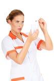 Νέος θηλυκός οδοντίατρος που κρατά έναν πρότυπο και οδοντικό καθρέφτη δοντιών Στοκ Εικόνες