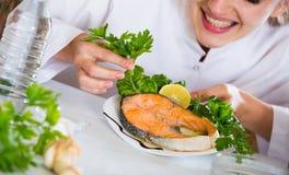 Νέος θηλυκός προϊστάμενος με τα τηγανισμένα ψάρια στο πιάτο Στοκ Φωτογραφίες