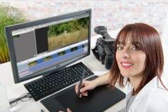 Νέος θηλυκός σχεδιαστής που χρησιμοποιεί τον υπολογιστή για την τηλεοπτική έκδοση στοκ εικόνα με δικαίωμα ελεύθερης χρήσης