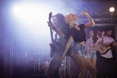 Νέος θηλυκός τραγουδιστής με τον αρσενικό κιθαρίστα που αποδίδει στο νυχτερινό κέντρο διασκέδασης Στοκ φωτογραφίες με δικαίωμα ελεύθερης χρήσης