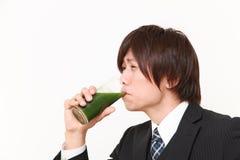 Νέος ιαπωνικός επιχειρηματίας με τον πράσινο φυτικό χυμό Στοκ φωτογραφία με δικαίωμα ελεύθερης χρήσης