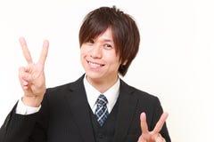 Νέος ιαπωνικός επιχειρηματίας που παρουσιάζει σημάδι νίκης Στοκ φωτογραφία με δικαίωμα ελεύθερης χρήσης