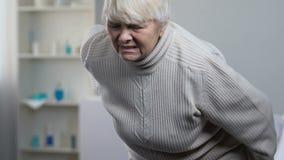 Νέος ιατρικός εργαζόμενος που βοηθά τον ανώτερο θηλυκό υφιστάμενο πόνο μέσα πίσω στη στάση επάνω φιλμ μικρού μήκους