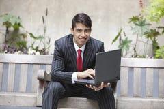 Νέος ινδικός επιχειρηματίας που χρησιμοποιεί το lap-top καθμένος στον πάγκο Στοκ Εικόνα