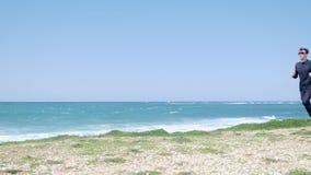 Νέος ισχυρός δρομέας σε ένα ίχνος κατά μήκος της παραλίας που φορά τη μαύρη αθλητική εξάρτηση απόθεμα βίντεο