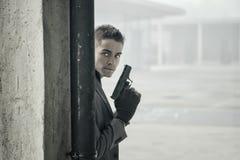 Νέος ιδιωτικός αστυνομικός ή αστυνομικός ή mobster σε μια αστική ρύθμιση που κρατά ένα πυροβόλο όπλο Στοκ Φωτογραφία