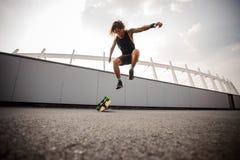 Νέος και ελκυστικός τύπος που πηδά στο longboard Στοκ φωτογραφία με δικαίωμα ελεύθερης χρήσης