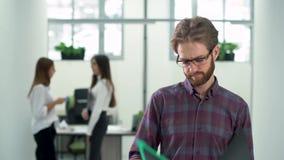 Νέος και σοβαρός τύπος που λειτουργεί το διευθυντή στο επιχειρησιακό γραφείο και την παραμονή που στρέφεται με τα έγγραφα και του απόθεμα βίντεο