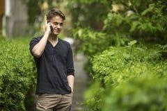 Νέος και όμορφος τύπος που μιλά στο κινητό τηλέφωνο υπαίθρια Φύση Στοκ εικόνες με δικαίωμα ελεύθερης χρήσης