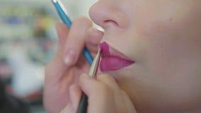 Νέος καλλιτέχνης makeup που εφαρμόζει το κραγιόν στα πρότυπα χείλια ` s απόθεμα βίντεο