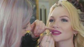 Νέος καλλιτέχνης makeup που εφαρμόζει το κραγιόν στα πρότυπα χείλια ` s φιλμ μικρού μήκους