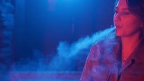Νέος καπνίζοντας ψεκαστήρας γυναικών στη λέσχη σε ένα ζωηρόχρωμο φως απόθεμα βίντεο
