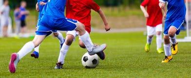 Νέος κατώτερος αγώνας ποδοσφαίρου Παίκτες που τρέχουν και που κλωτσούν τη σφαίρα ποδοσφαίρου στοκ εικόνες