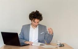 Νέος καυκάσιος επιχειρηματίας που διαβάζει τις σημειώσεις του, που κάθονται στο γραφείο του μπροστά από τον κενό σαφή τοίχο στοκ φωτογραφίες