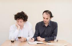Νέος καυκάσιος επιχειρηματίας που καθιστά ένα πρόσωπο στο συνάδελφό του στην αρχή με το ελαφρύ υπόβαθρο Στοκ Εικόνα
