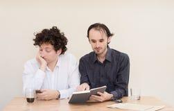 Νέος καυκάσιος επιχειρηματίας που καθιστά ένα πρόσωπο στο συνάδελφό του στην αρχή με το ελαφρύ υπόβαθρο Στοκ Εικόνες