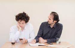Νέος καυκάσιος επιχειρηματίας που καθιστά ένα πρόσωπο στο συνάδελφό του στην αρχή με το ελαφρύ υπόβαθρο Στοκ εικόνα με δικαίωμα ελεύθερης χρήσης
