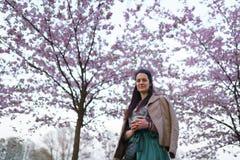 Νέος καφές κατανάλωσης γυναικών από ένα φλυτζάνι εγγράφου που φορά τη σμαραγδένια φούστα χρώματος - ζωηρόχρωμο άνθος κερασιών sak στοκ εικόνα